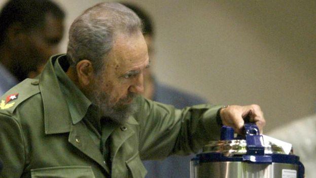 El expresidente cubano, Fidel Castro, sostiene una olla reina de fabricación china. (EFE)