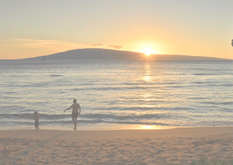 Phot man and boy on beach at sunset
