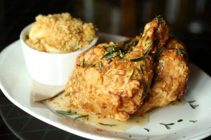 Venkman's Cast Iron Fried Chicken is drizzled with hot sauce honey and served alongside pimento cheese and shells.