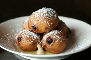 Puffy blueberry ricotta donuts are piled high, served atop lemon curd and dusted with powdered sugar.