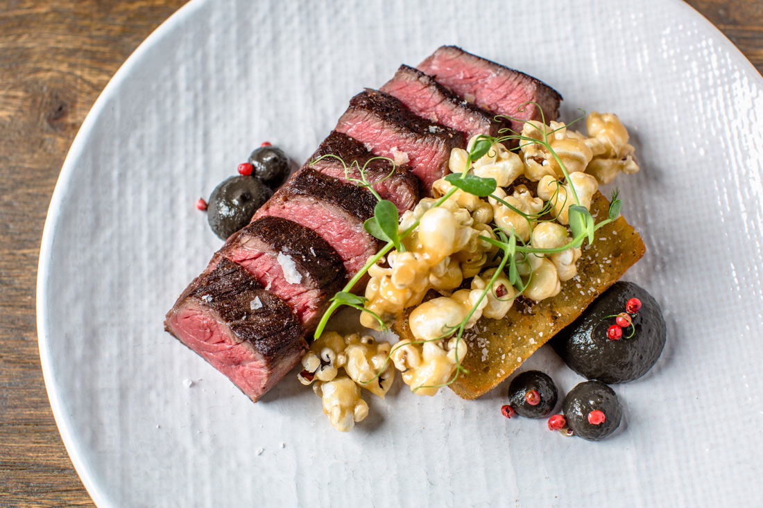 Griddled beef coulotte is served with a potato hash brown, garlic confit, huitlacoche and porcini caramel corn.