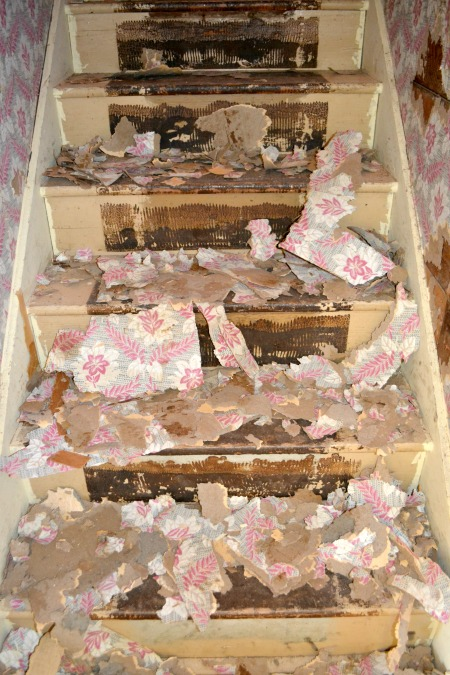 A view on a stairwell of wallpaper remnants in piles after being removed