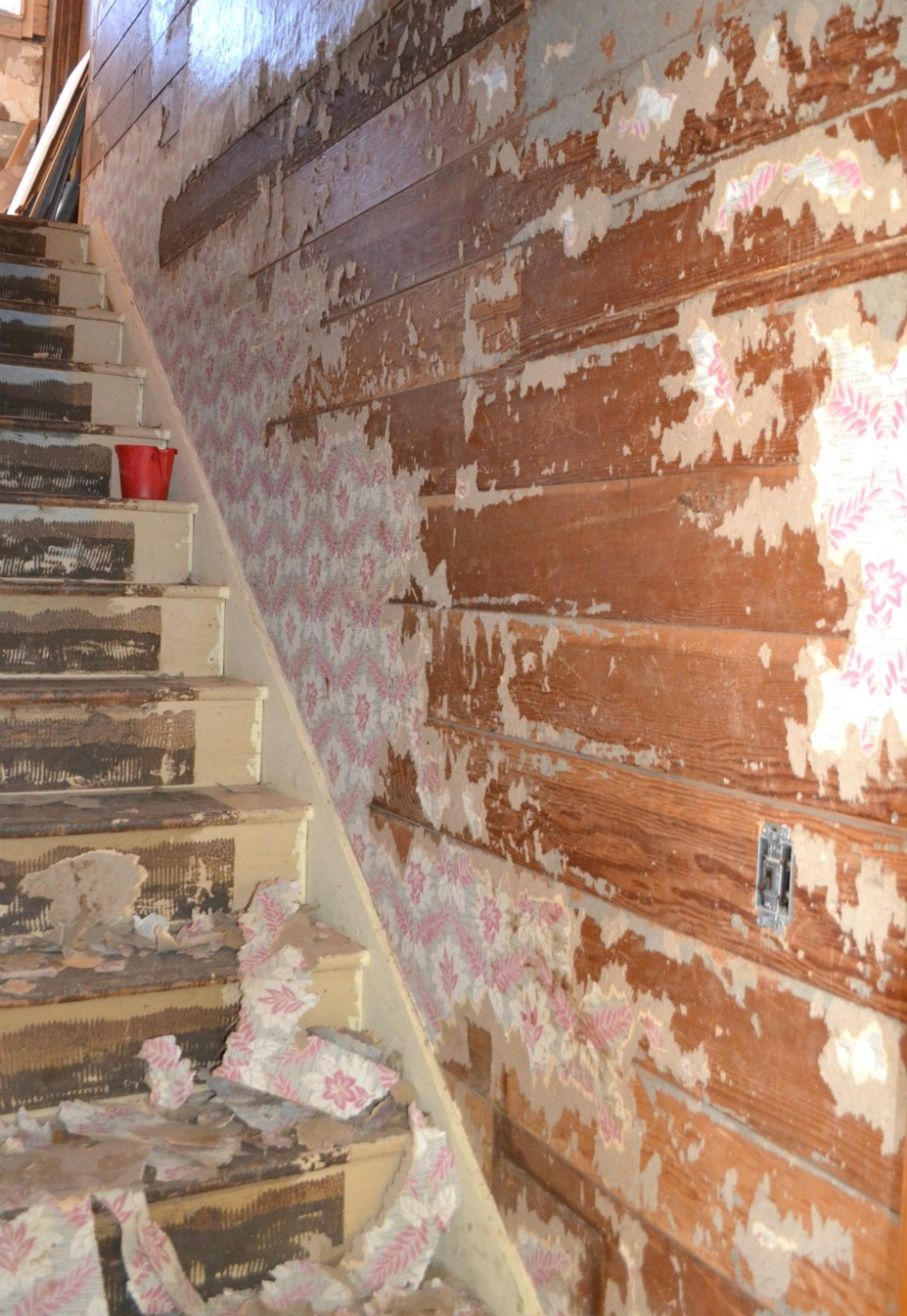 A view up a wood stairwell where the original wood is exposed with wallpaper remnants on the stairs