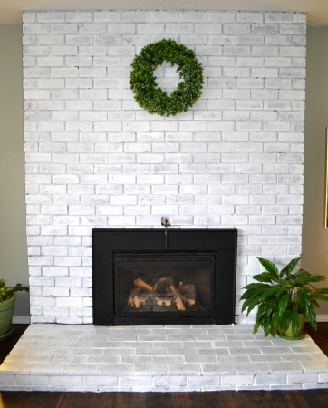 Whitewashing a fireplace completely transformed our living room from outdated to fresh and modern with a cozy farmhouse feel