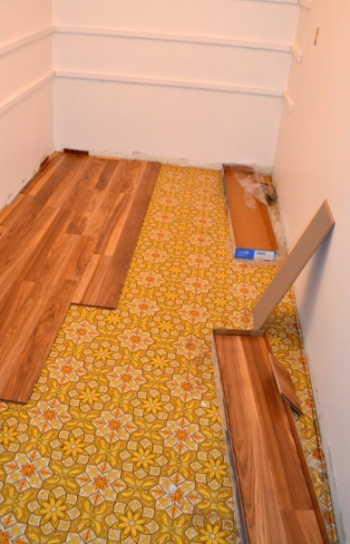 Installing laminate hardwood over laminate sheeting