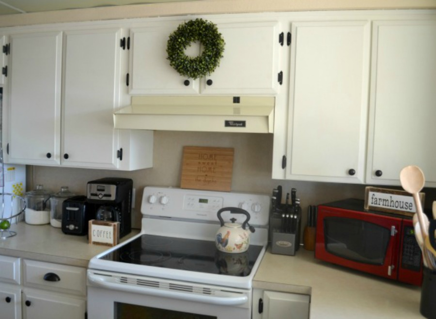 Original kitchen cabinets given an update with paint and new hardware for a light farmhouse look