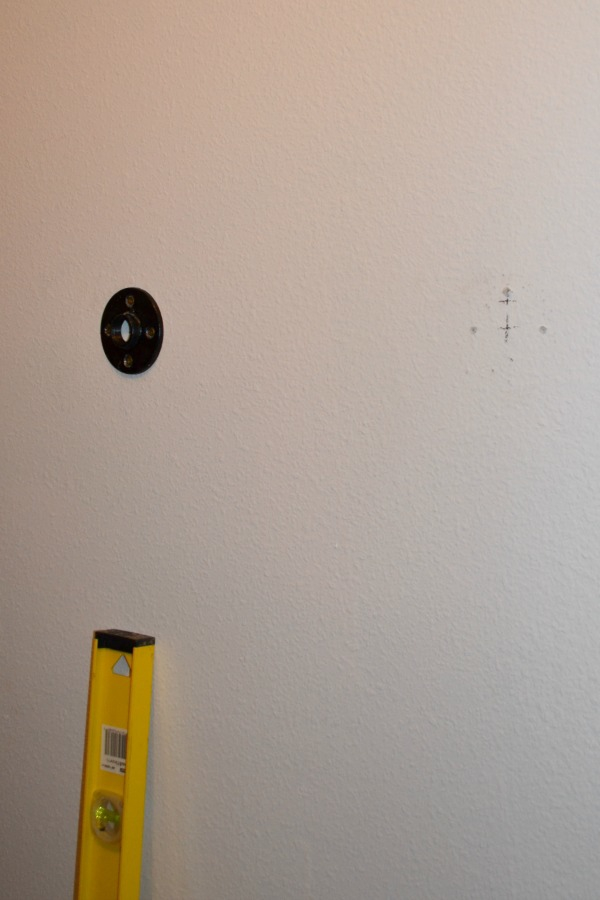 Attaching black iron pipe bases to the wall for pipe shelves