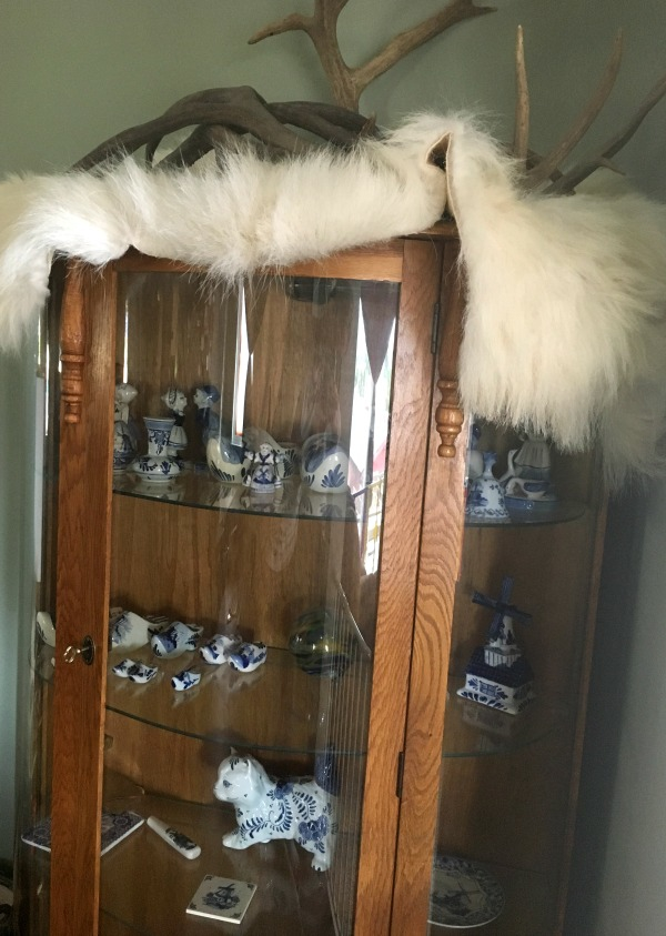Glass curio cabinet displaying a delft blue collection