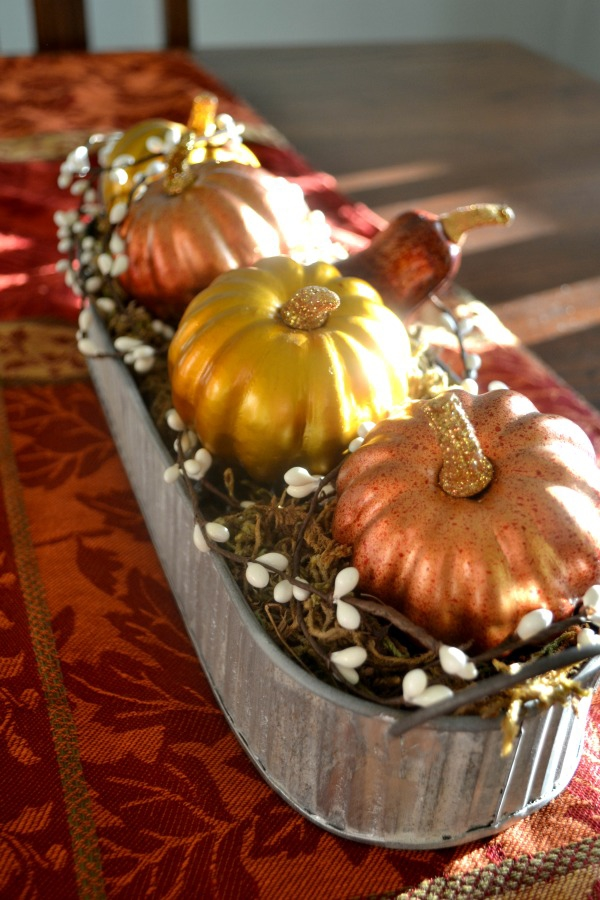 Metallic pumpkins and a metal trough complete a rustic centerpiece for any table