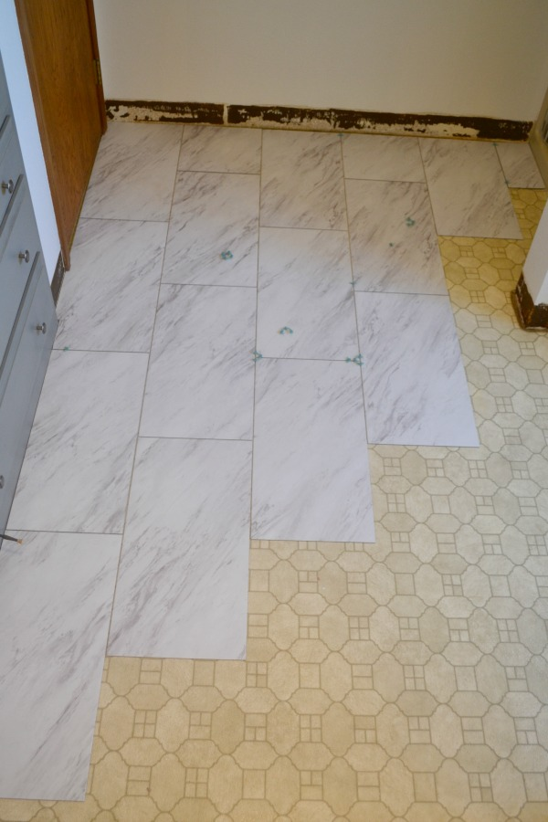 Vinyl tile installation in progress will transform any bathroom