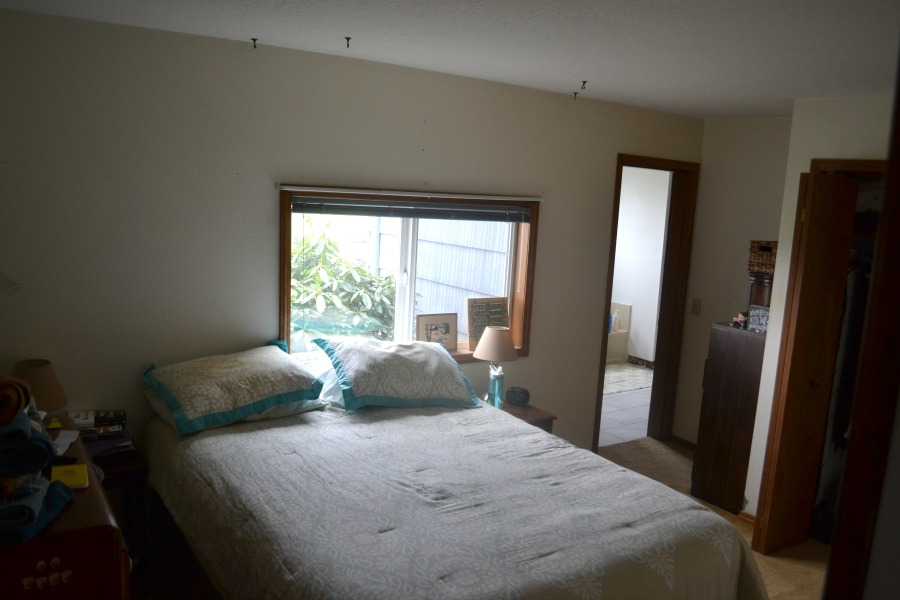 View from the end of the bed toward a small horizontal window and a door leading to a bathroom on the far right
