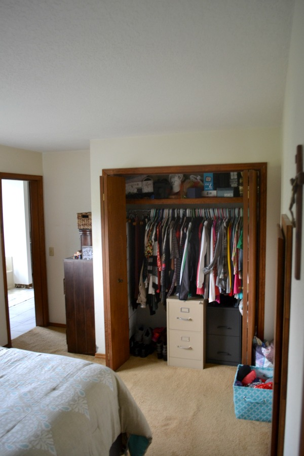 A view of open bifold closet doors with hanging clothes on a rod, brown carpet and two file cabinets in the middle of the closet