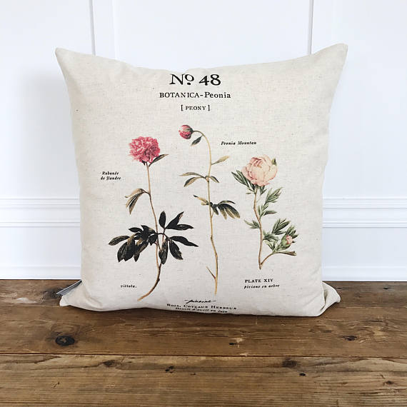 A linen pillow form with a peony picture in pink on a wood floor