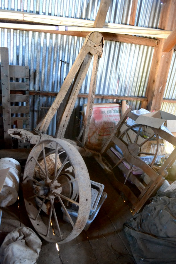 A dusty pile of old metal wagon wheels, a bed frame and other vintage treasures