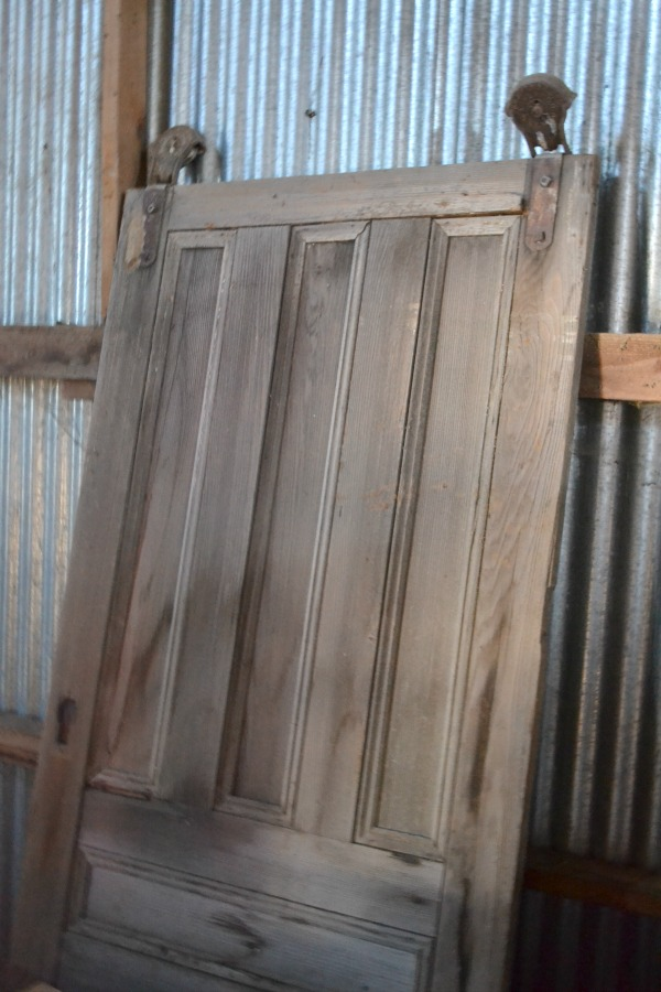 An old wood sliding barn door leaning against the galvanized metal wall of the barn