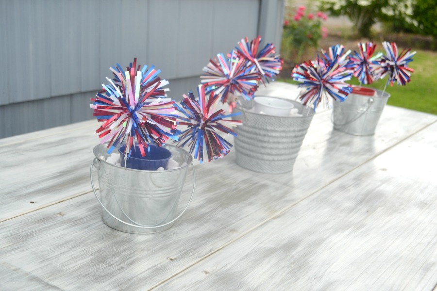 A side view of 3 buckets sitting on a table with candles in the center and red, white and blue pom-poms out of each bucket