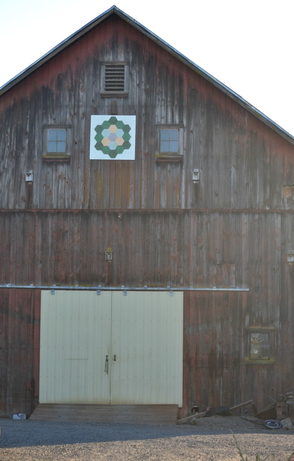 A white quilt square with a flower design on a faded red barn from far away