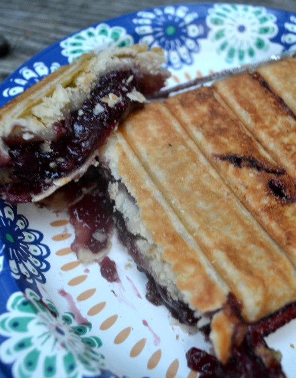A cut piece of pie sitting on top of the rest of the pie with cherry filliing sitting on a paper plate