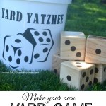 """A white bucket with a dice picture and the words """"yard yatzhee"""" sitting next to wood stacked dice in a green lawn"""
