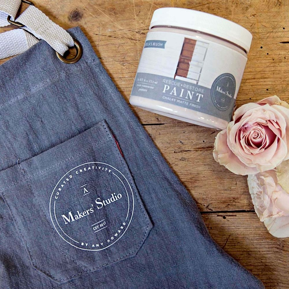 A denim blue apron laying flat with a jar of rescue restore paint on it's side on a wood background with a pink rose