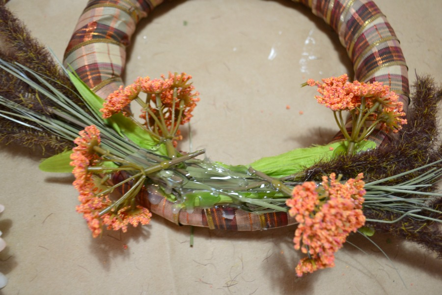 A ribbon covered foam ring with faux orange berry flowers hot glued over top
