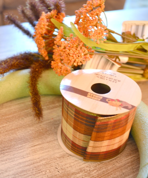 A spool of ribbon sitting inside a foam wreath with faux flowers bunched up in the background