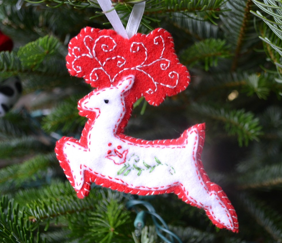 A red and white embroidered reindeer hanging on a Christmas tree would be easy for a beginner craft project