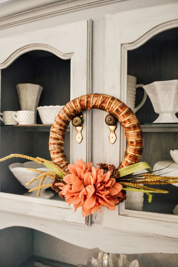 An orange, brown and gold ribbon wrapped styrofoam wreath ring with pink and mauve flowers on the bottom and green and yellow grasses sticking out from each side of the flowers