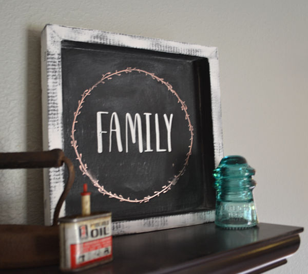 The word family on a black sign surrounded by a copper leaf design with a white background sitting on floating shelf