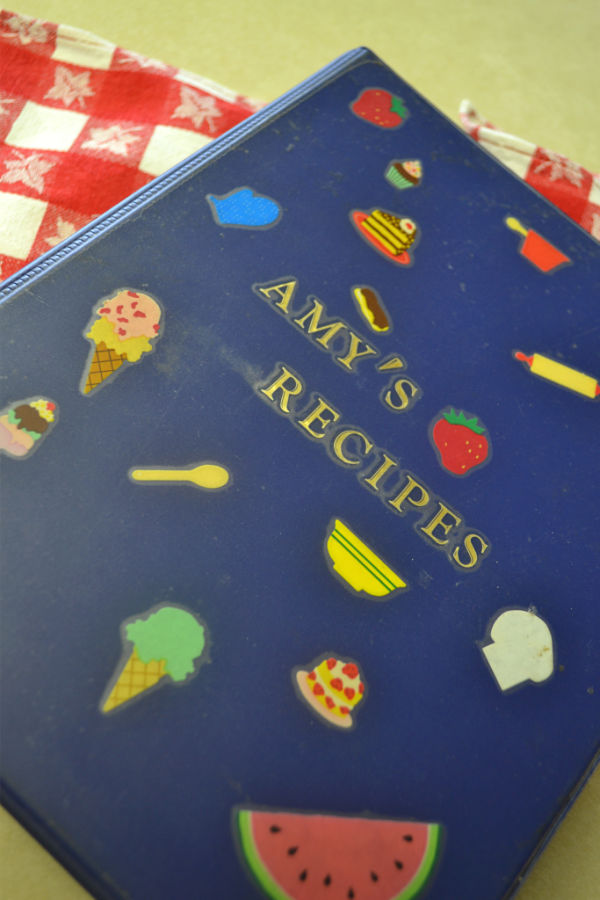 "A blue binder covered with food stickers with the words ""Amy's Recipes"""