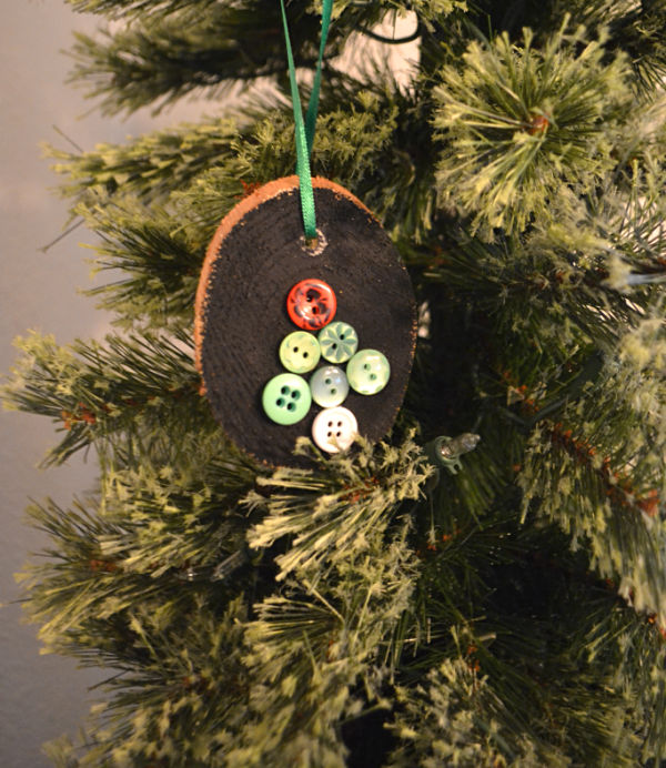 A green Christmas tree with a wood slice ornament hanging by a green ribbon with multi-colored buttons in the shape of a tree