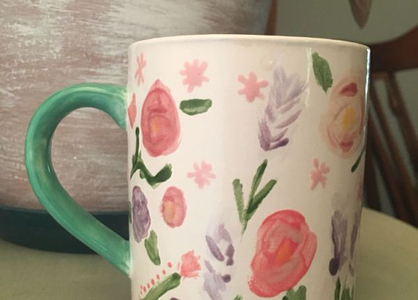 A fired and glazed completed ceramic mug with flowers and a green handle sitting ona green table with a whitewashed pot in the background