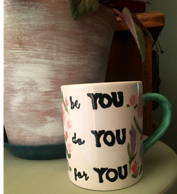 """A completed fired and hand-painted mug with the words in black """"be you, do you, for you"""""""