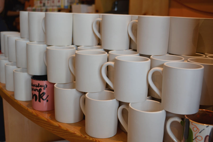 A stack of white mugs that are piled three mugs high and about five rows deep