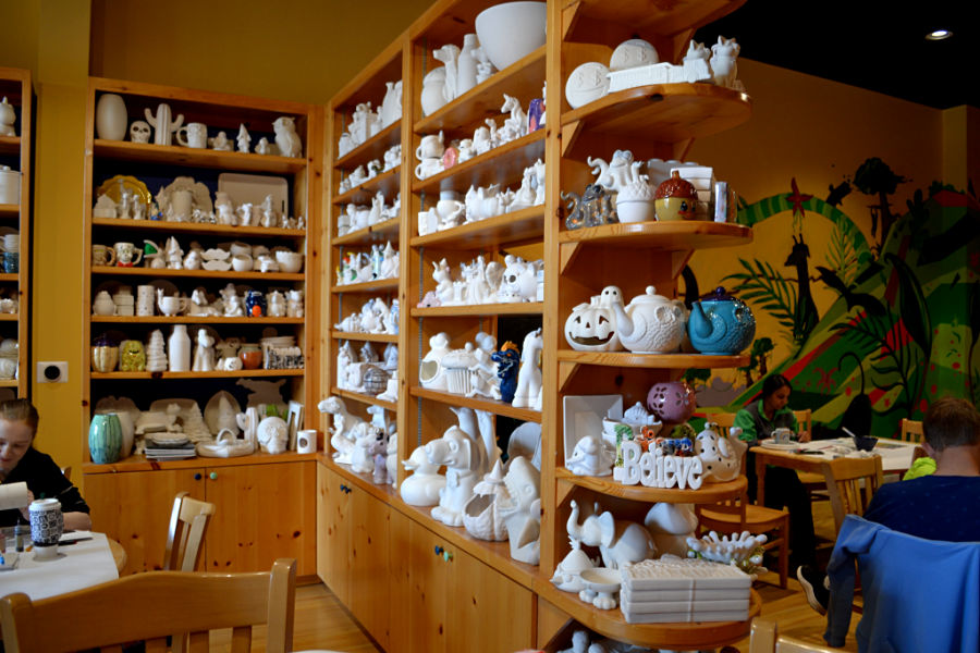 A side view of shelves at Color Me Mine ceramic studio stacked with unpainted ceramic pieces