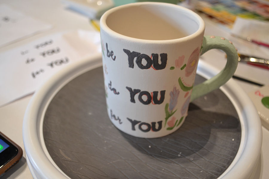 "A painted mug on a lazy susan with the words ""be you, do you, for you"" with a green handle and flowers"