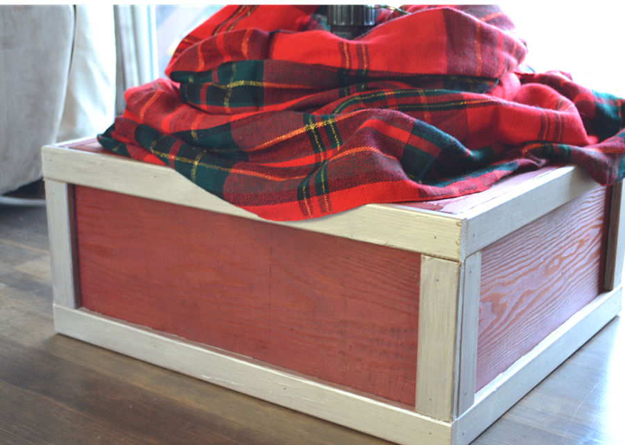 A red and metallic ivory stained wooden box with a red plaid cloth around the base of a fake tree