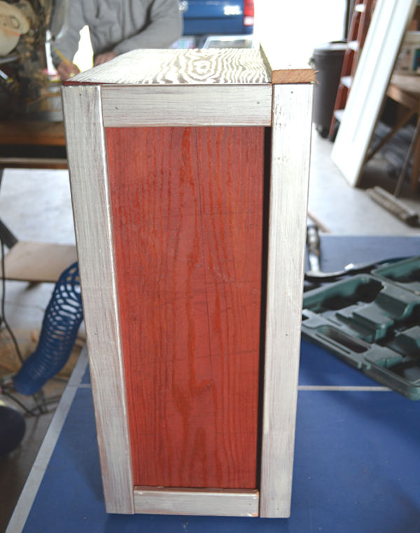 The side view of a wooden box stained red with ivory pearl trim on all sides