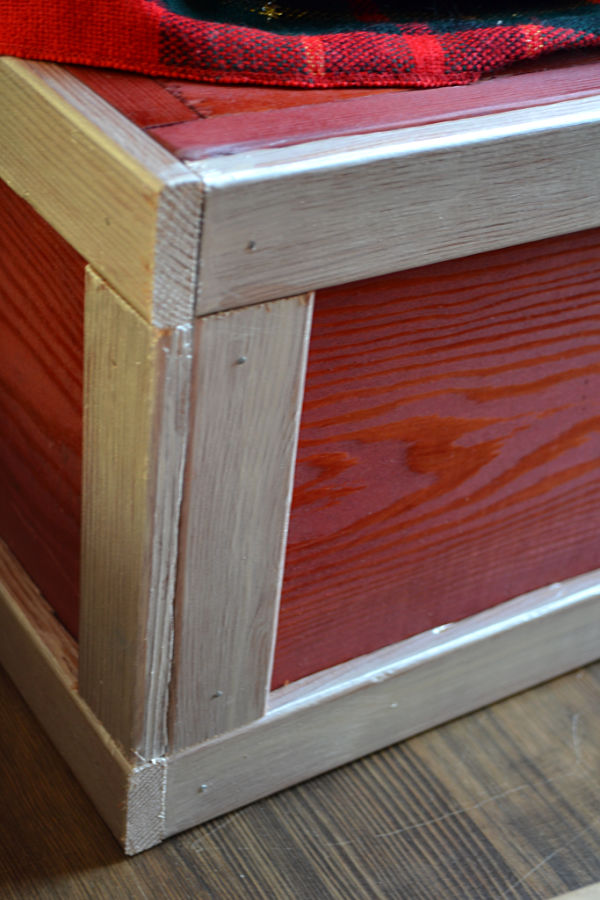A close up photo of the corner of a wooden box stained red with an ivory painted trim border on a dark wood floor
