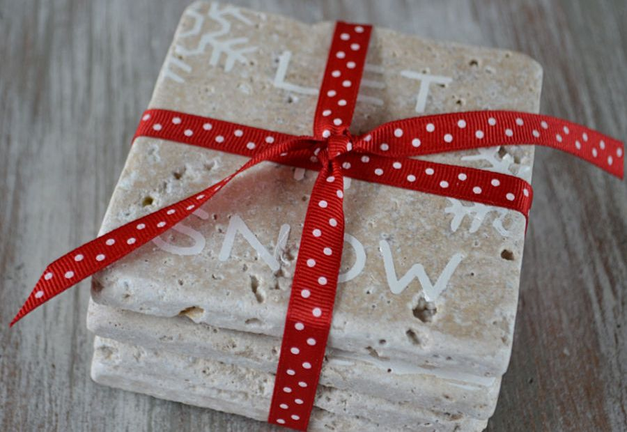 Four stone coasters stacked on top of each other tied with a red ribbon with polka dots on it