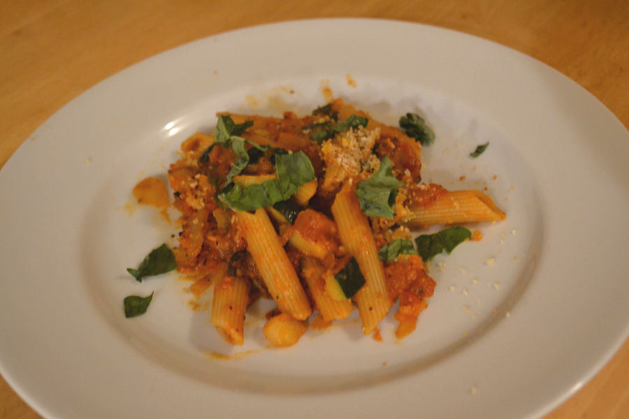 A white plate with a penne noodle and red sauce with basil topping