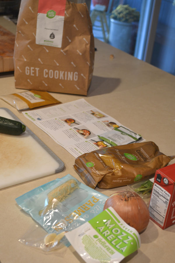A countertop with an instruction page and several ingredients laid out next to a white cutting board and a paper bag