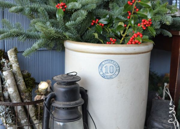 A vintage crock filled with evergreen boughs next to a vintage lantern and a wire basket filled with firewood