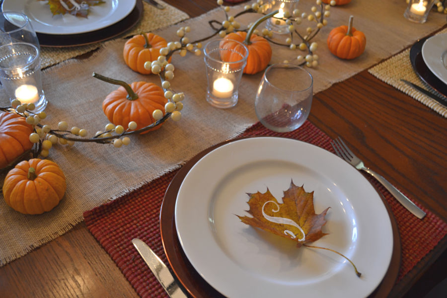 A maple leaf with a ChalkArt initial sitting on a white plate with a burlap runner with small pumpkins and white bead garland with a candle in a glass