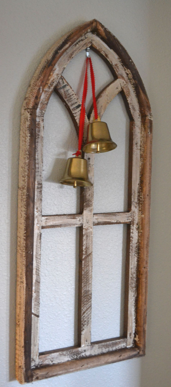 A chippy wood church window hung on a wall with gold bells hung by red ribbon displayed in front