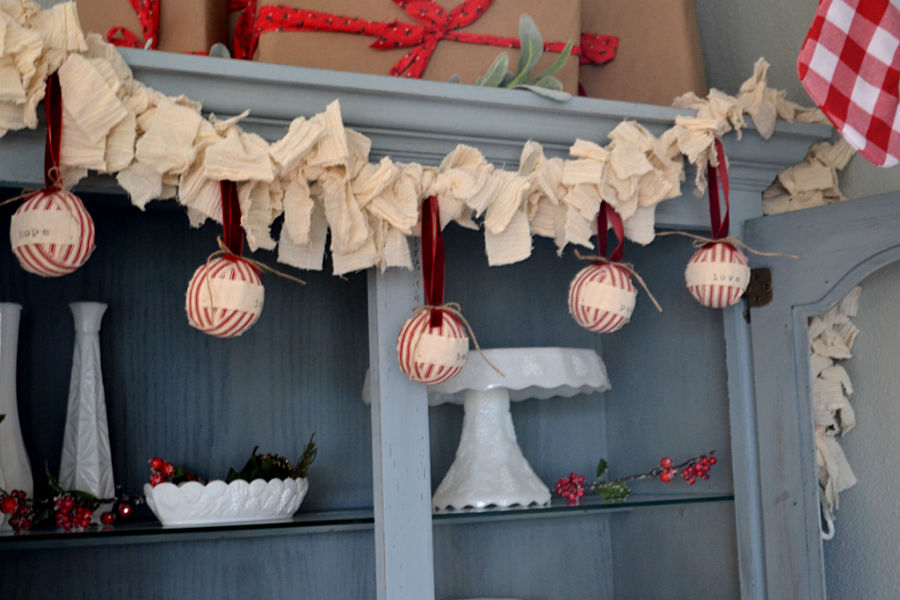 Off white linen fabric garland with red and whtie ticking Christmas balls hanging from it with a milk glass collection displayed below