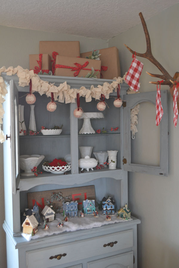 A blue gray hutch with doors open on top to reveal a white milk glass collection with garland hanging on top and a Christmas village