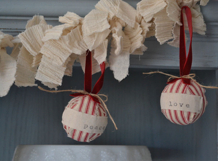 A close up of white linen fabric strips with red and white ball ornaments hung from the garland