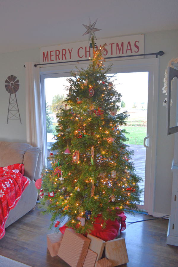 A tall Christmas tree in the center of a sliding window with a large Merry Christmas sign above the door and red blanket displayed on the couch to the left