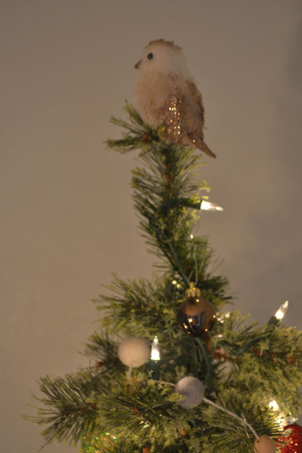 A fake bird on a clip is attached to the top of a fake pencil Christmas tree